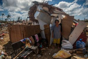 A Guiuan woman stands outside of her makeshift shack in the aftermath of Super Typhoon Haiyan. (US Government via Wikimedia Commons)